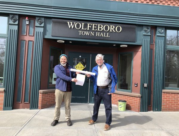 picture of Josh Arnold and Dave Bolduc holding signed building permit for Makers Mill in front of Wolfeboro Town Hall